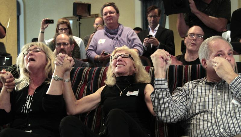 Supporters of Amanda Knox react as they watch a television news broadcast about her appeal verdict as they sit in a hotel suite in downtown Seattle on Monday.