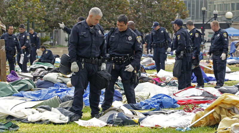 Oakland police officers sift through possessions left behind by Occupy Oakland protestors Tuesday in Oakland, Calif. Occupy Oakland protestors were evicted from Frank H. Ogawa plaza early this morning by police in riot gear.
