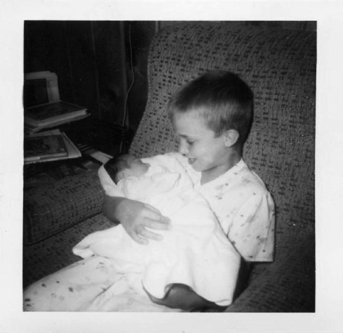 Dell May, at age 7, holds his new-born brother Ben