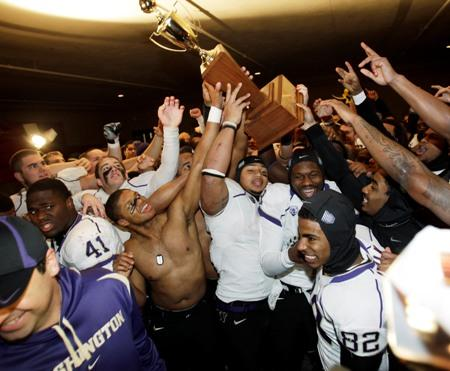 Washington players celebrate with the Apple Cup trophy after they defeated Washington State 35-28 last year in Pullman.