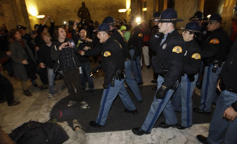 Washington State Patrol troopers use tasers to control a crowd of protestors who rushed at the locked doors of the Capitol and attempted to let people inside after the building was closed, in Olympia, Wash., on Monday.