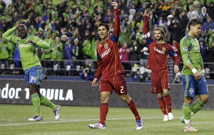 Real Salt Lake's Tony Beltran (2) and Kyle Beckerman, center, celebrate a play as Seattle  Sounders' Jhon Kennedy Hurtado, left, and Fredy Montero, second from right, react. The Seattle Sounders won the game 2-0, but were knocked out of the playoffs.