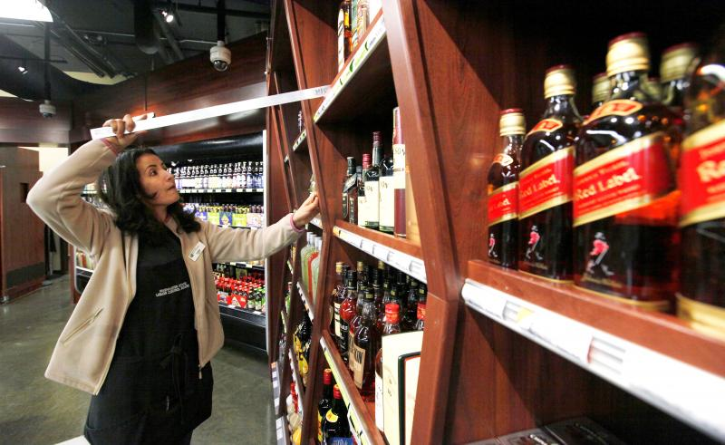 Control Board clerk Lidia Giusti uses a metal bar to straighten rows of liquor on shelves in Oct. 31 at a new state liquor store in the West Seattle neighborhood of Seattle.