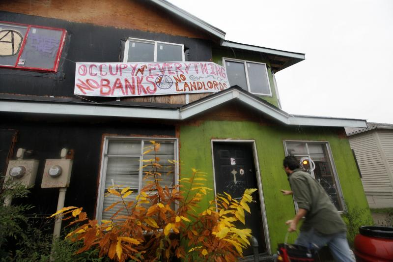 An Occupy Seattle protester, who declined to be identified, enters a formerly boarded-up duplex Nov. 22 that protesters have taken over in Seattle's Central District to protest foreclosures.