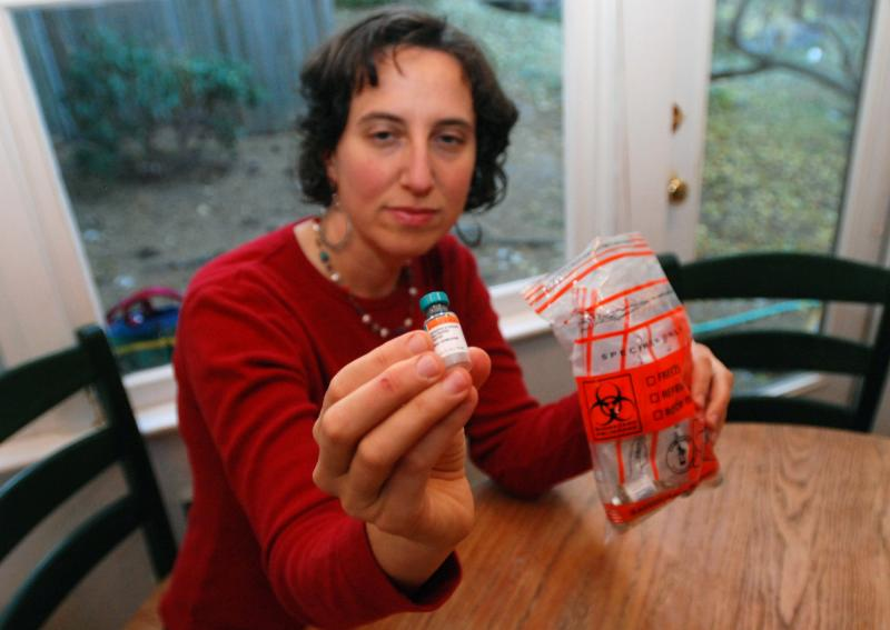 Sitting in her home in Ashland, Ore., earlier this month Jennifer Margulis shows off empty vials of vaccine that she saves in case one of her children has a bad reaction. Like many parents, she is concerned about the right schedule for vaccinations.