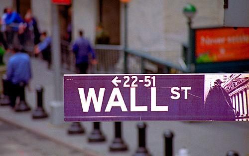 Wall St. sign with blue jacketed traders on their lunch break in the background.