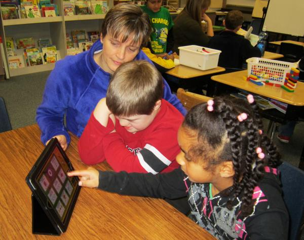 Christine Dunbar works with Parkwood Elementary students Jeffrey Coe and Shahiira Harrison on phonemic awareness skills using a tic-tac-toe game on the iPad.