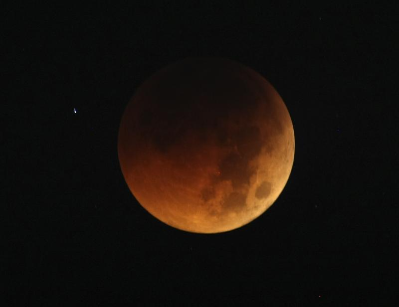 In this Thursday June 16, 2011 file photo, the moon exhibits a deep orange glow as the Earth casts its shadow in a total lunar eclipse as seen in Manila, Philippines, before dawn. The last total lunar eclipse of the year is Saturday, Dec.