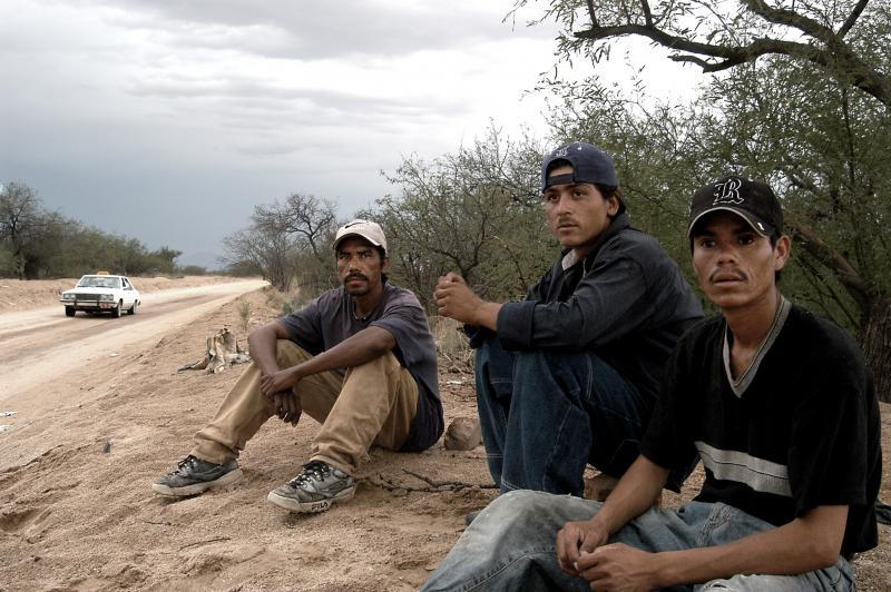 Central American migrants wait for nightfall just south of the U.S. border outside Sasabe, Mexico.