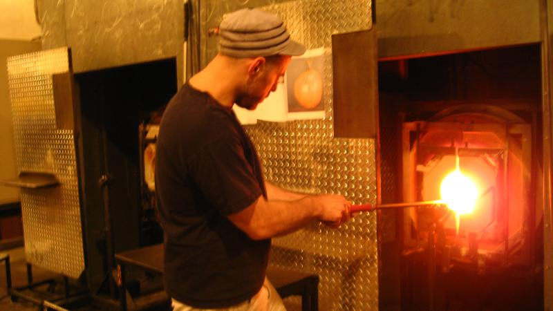 Jason Christian, the head gaffer at Seattle Glassblowing Studio in Belltown, dips a long pipe into a kiln.