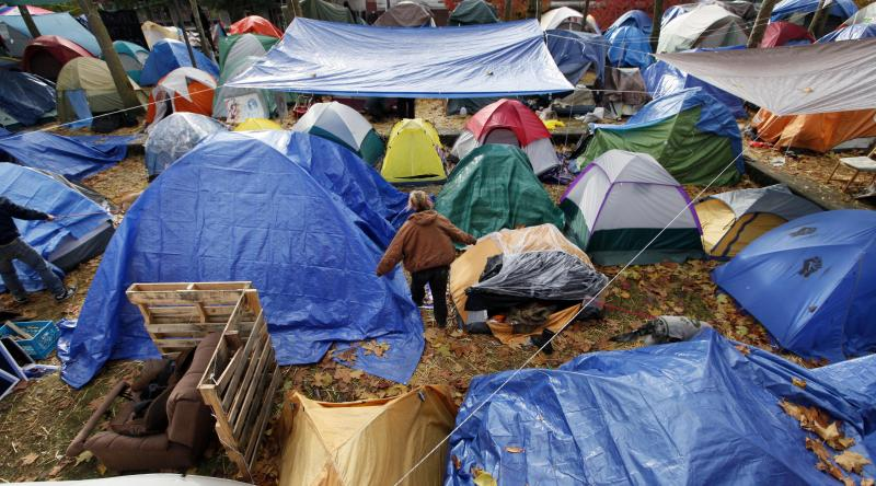 A camper at Occupy Seattle pulls on a jacket and walks among the dozens of tents there at Seattle Central Community College Nov. 15. A judge says they all have to go.