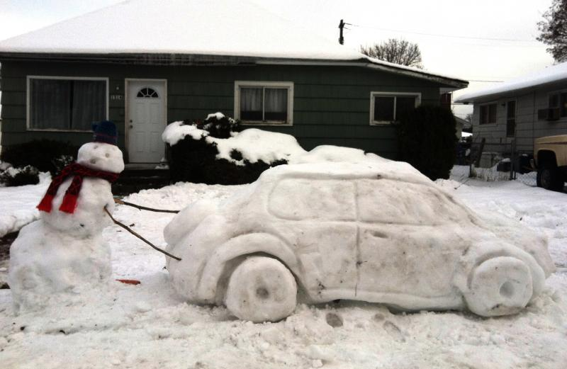 A Coeur d'Alene, Idaho snowman is among many Inland Northwest residents whose cars are stuck in the snow.