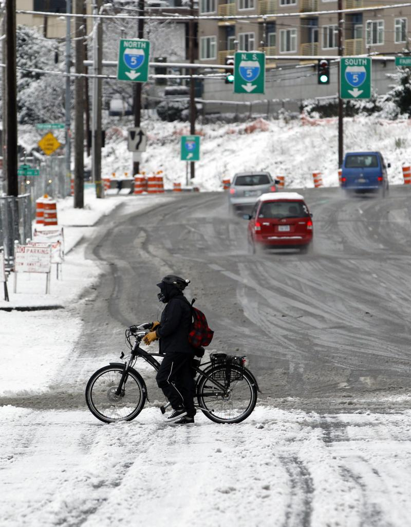 bicyclist walks as he makes his way across a snowy roadway near Interstate 5 just north of downtown Seattle Sunday afternoon.
