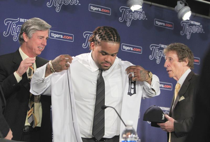 Detroit Tigers president, CEO and general manager Dave Dombrowski, left, helps new Tigers first baseman Prince Fielder with his uniform as team owner Mike Ilitch looks on during a baseball news conference at Comerica Park in Detroit on Thursday.