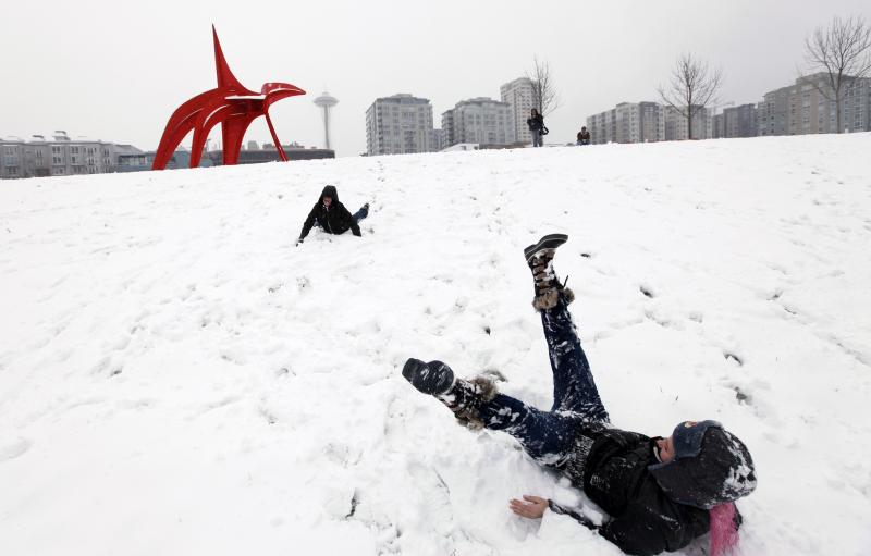 Heidi Hunt, right, and Alexis Nasya Prass playfully tumble down a snow-covered hill at the Olympic Sculpture Park near Wednesday in Seattle.