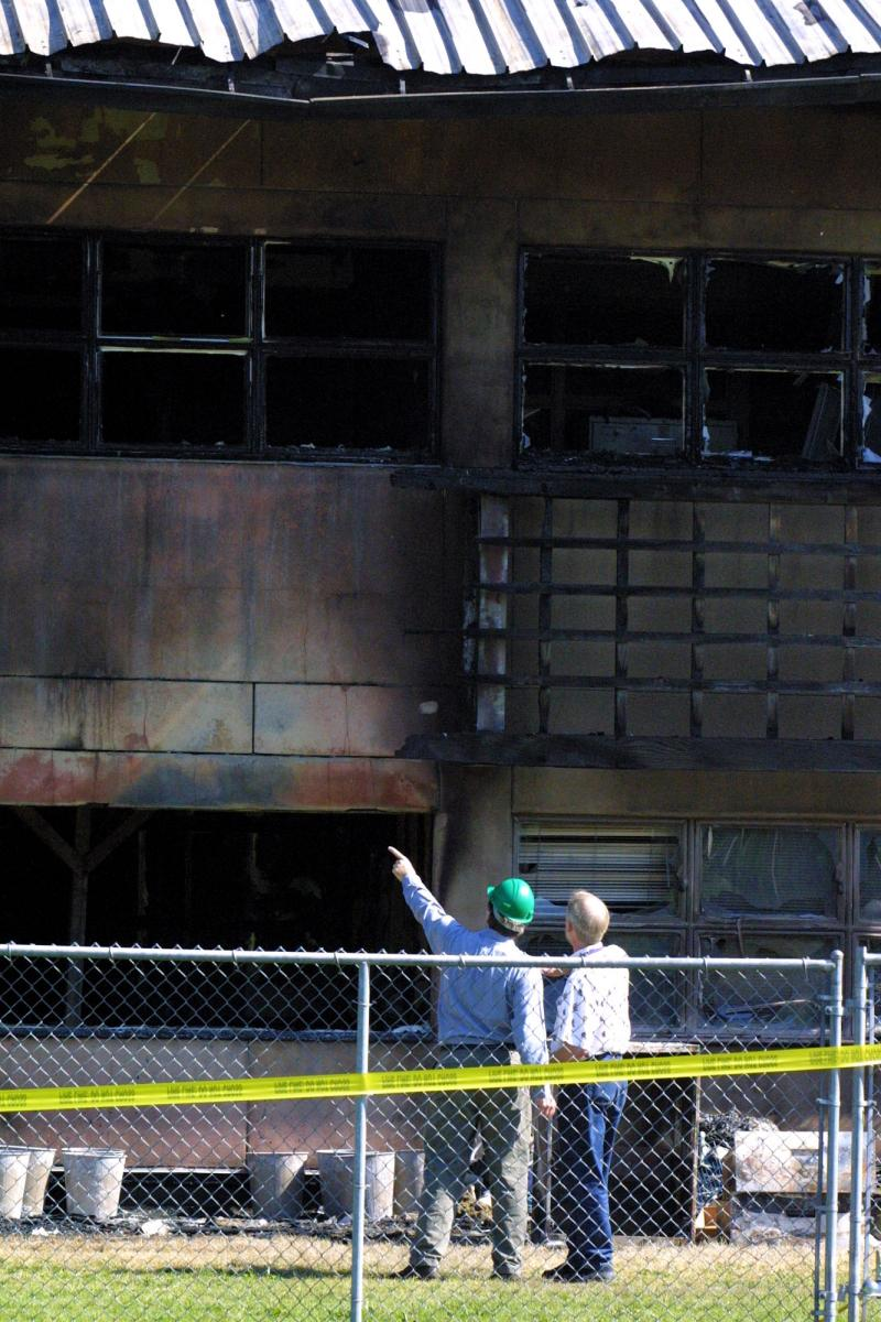Thomas M. Hinckley, right, and an unidentified person at left, survey fire damage at the University of Washington's Center for Urban Horticulture in Seattle, in this May 23, 2001 file photo.