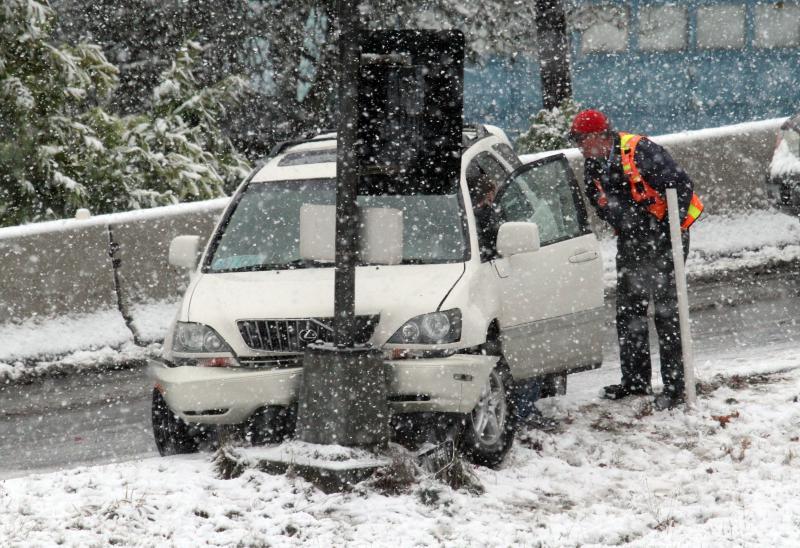 An Oregon Department of Transportation employee checks on a crash victim in Beaverton, Ore., on Tuesday.