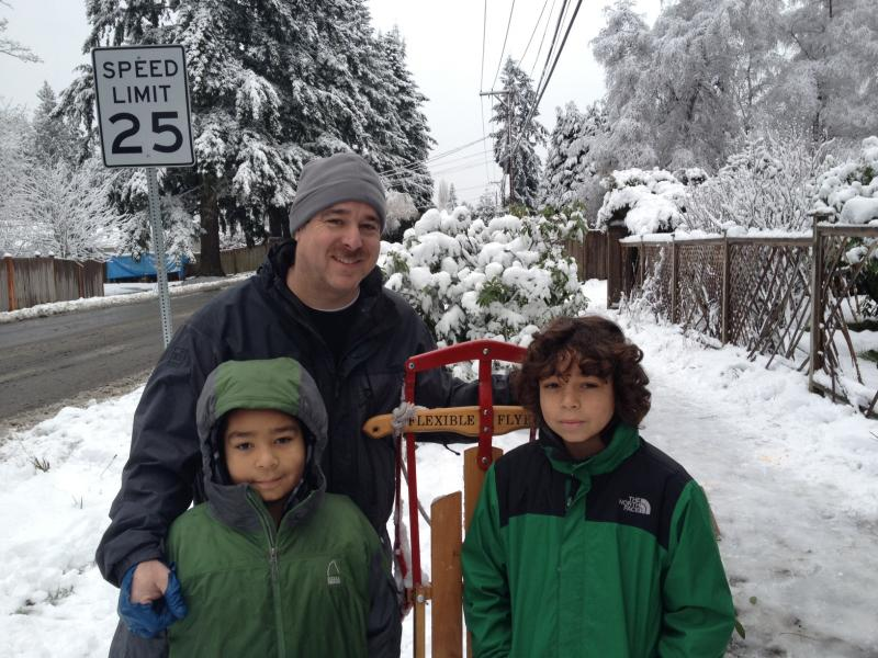 Matthew Ortiz and his sons, Lorenzo (l) and Carlos leave a sledding hill near Meridian Street