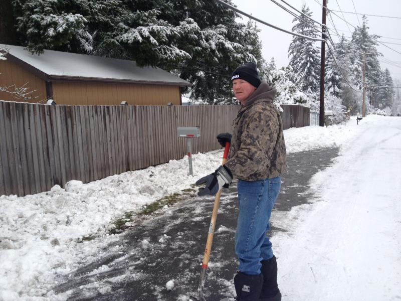 Brian Scollard takes a break from shoveling outside his house in Bothell. He likes the de-icer Seattle has been using, but isn't sure if it's good for the environment.