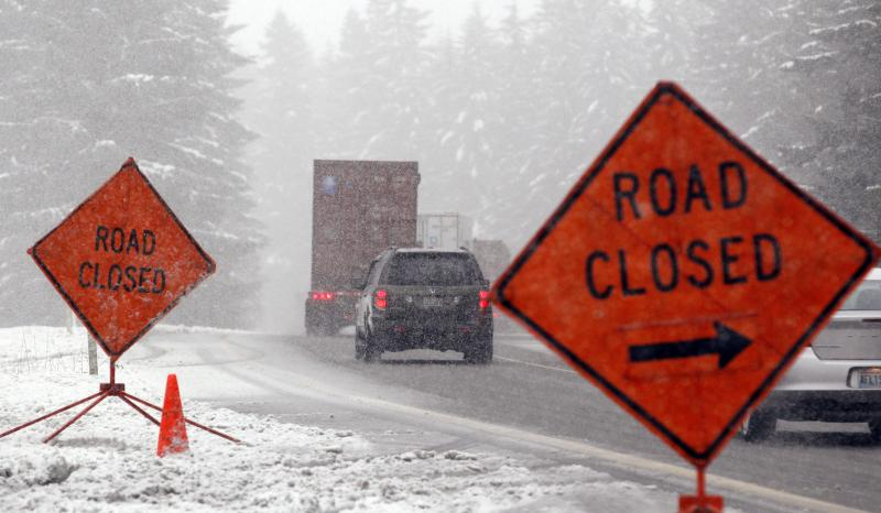 Trucks and other motorists make their way off of Interstate 90 where the pass ahead was closed Tuesday near North Bend, Wash. Snow has been falling steadily in various parts of western Washington since the weekend.