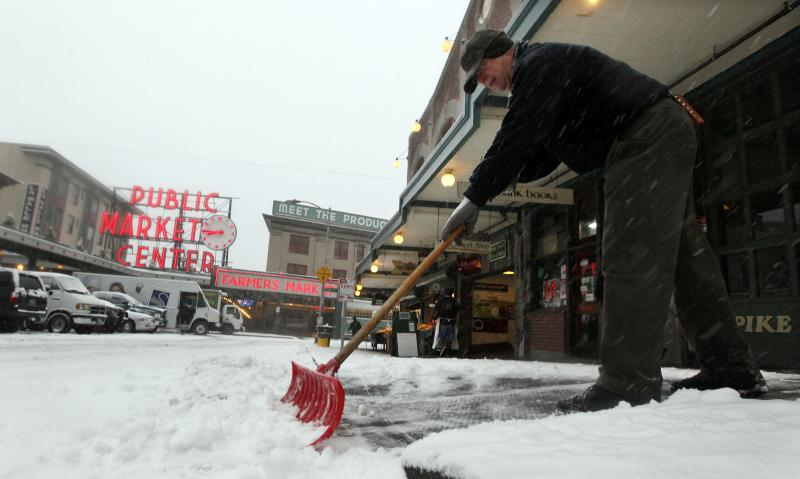 Jeff Jarvis, facilities manager at the Pike Place Market, shovels snow at the landmark site on Wednesday in Seattle.