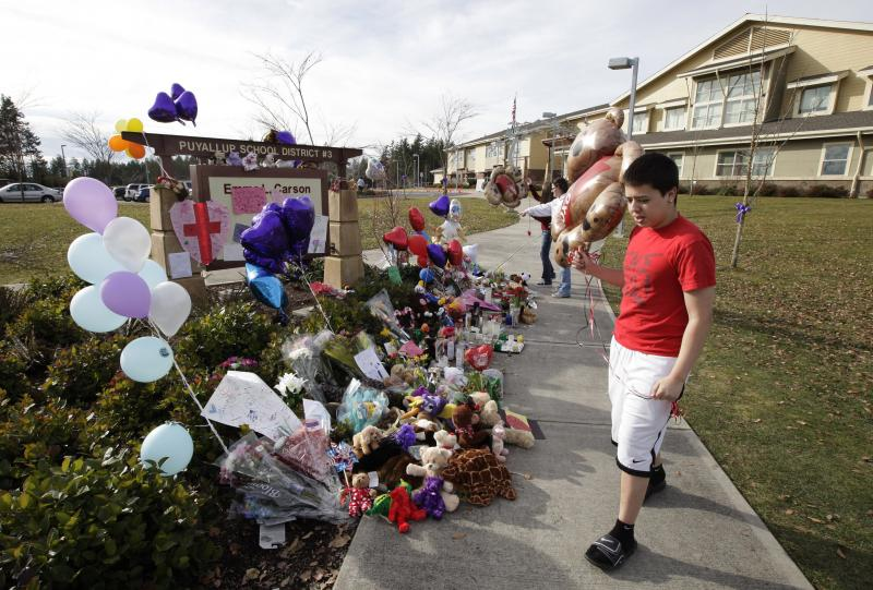Alex Ramirez, 17, brings a balloon to a growing memorial to Charlie and Braden Powell, Tuesday, Feb. 7, 2012, at Carson Elementary School in Puyallup, Wash., where Charlie attended school.