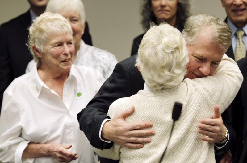 Jane Abbott Lighty, left, looks on as her partner of 35 years, Pete-e Petersen, hugs Sen. Ed Murray, D-Seattle, on Monday in Olympia, Wash., after hearing the news that the state Senate had enough votes to pass a same-sex marriage law.
