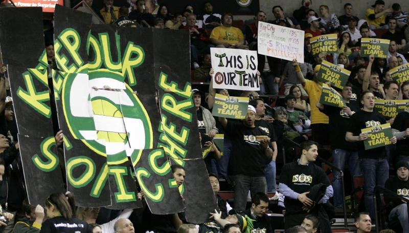 In this March 24, 2008 file photo, Seattle SuperSonics fans hold signs in favor of keeping the NBA basketball team in Seattle during the first period of a basketball game against the Portland Trail Blazers at KeyArena in Seattle.