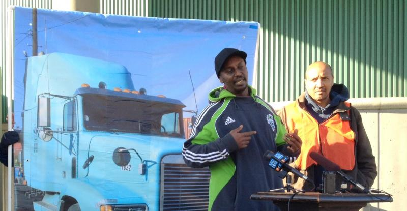 Fuad Eltayeb (l) and Yemane Berhane have stopped driving their short-haul trucks to terminals at the Port of Seattle. They say hundreds of cargo drivers like them face unsafe conditions. Often, the trailer loads they pick up are too heavy or insecure.