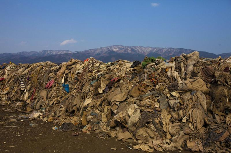 This file photo taken Tuesday Feb. 21, 2012 shows clothing lying in heaps at the site of a neighborhood destroyed by the 2011 earthquake and tsunami, in Rikuzentakata, Japan. Scientists believe ocean waves carried away 3-4 million tons.