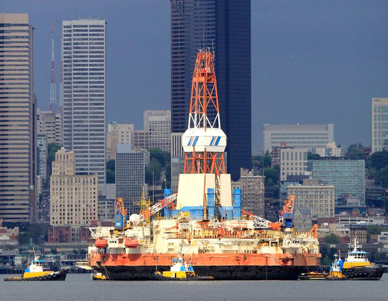 """The floating oil-drilling platform """"Kulluk"""" is seen briefly bathed in light as it passes an otherwise cloudy and dark downtown Seattle in July 2011."""