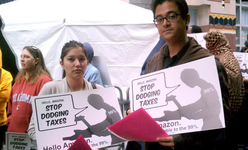 Priscilla Moreno and David Mendoza with Puget Sound SAGE came out Thursday morning to protest Amazon's tax policies.