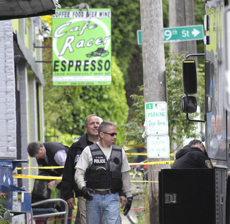 Seattle police officers walk outside a cafe just north of the University District where five people were shot on Wednesday.