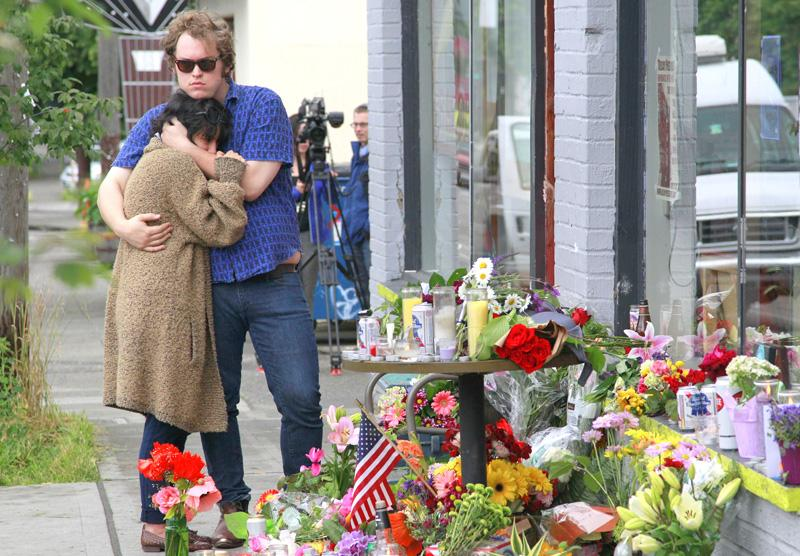 Jonny and Ali, who both declined to give their last names, comfort each other Thursday at the scene of where a gunman killed four people and severely wounded another.