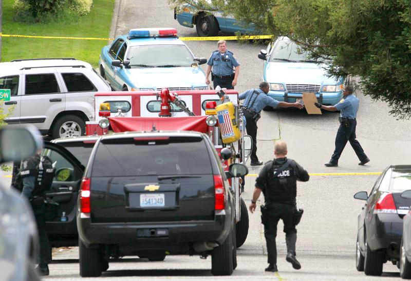 Police and other emergency responders fill an intersection at the scene where a man who was believed to have shot and killed five people and wounded one earlier in the day shot himself Wednesday in the West Seattle neighborhood of Seattle.
