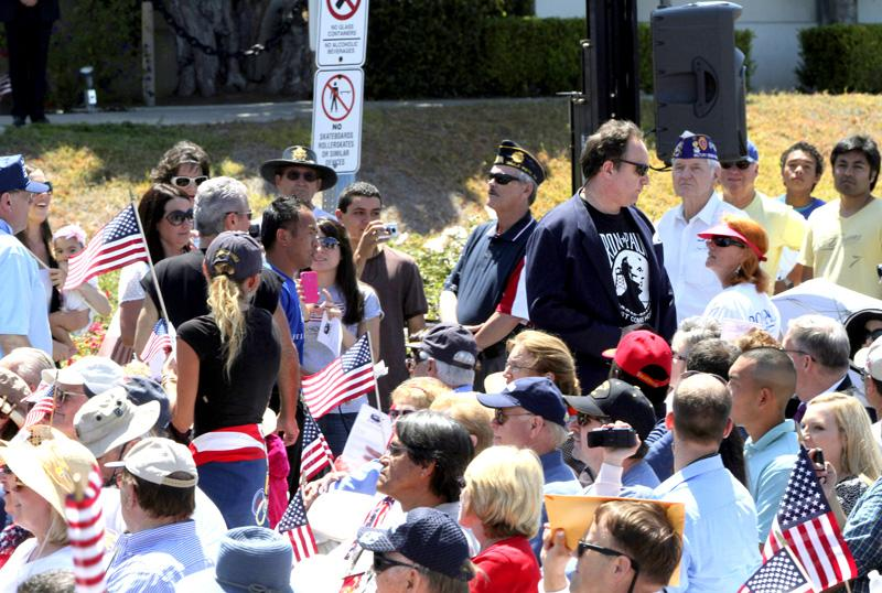 A man, in black with a Ron Paul shirt, leaves after interrupting Sen. John McCain, R-Ariz., making a pitch for Mitt Romney, at the Veterans Museum & Memorial Center last month in San Diego.