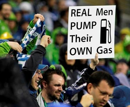 Fightin' words: Sounders fans cheer during a match against the Portland Timbers May 14, 2011, in Seattle. The sign shown refers to an Oregon law that requires gas station attendants, rather than motorists, to pump gas.