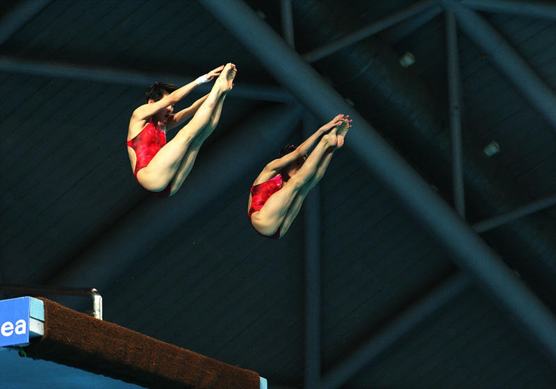 Two athletes perform a 10-meter synchronized platform dive at an earlier women's double Shimi Tai championship in China.