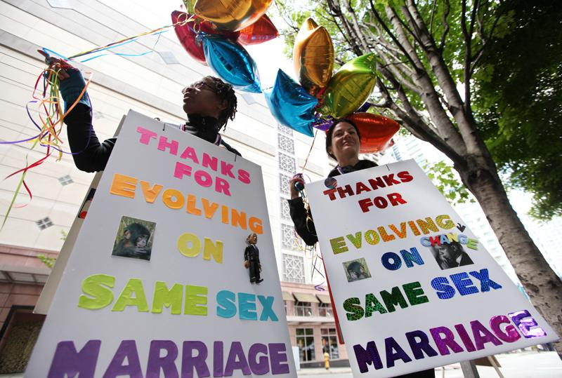 Marriage equality supporters Teri McClain, left, and Mary Beth Brotski stand with signs supporting President Barack Obama outside a fundraising event for the president on May 10 in Seattle. Will this social issue dominate the elections?