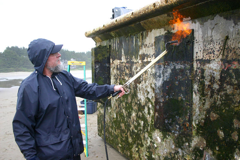 In this photo provided by the Oregon Park and Recreations Department, an unidentified worker burns off debris from the Japanese dock float on Thursday.