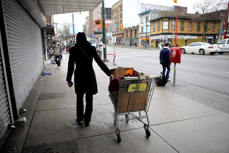 A woman wheels her cart along West Hastings Street in Vancouver, British Columbia, in 2010. A lonely place.
