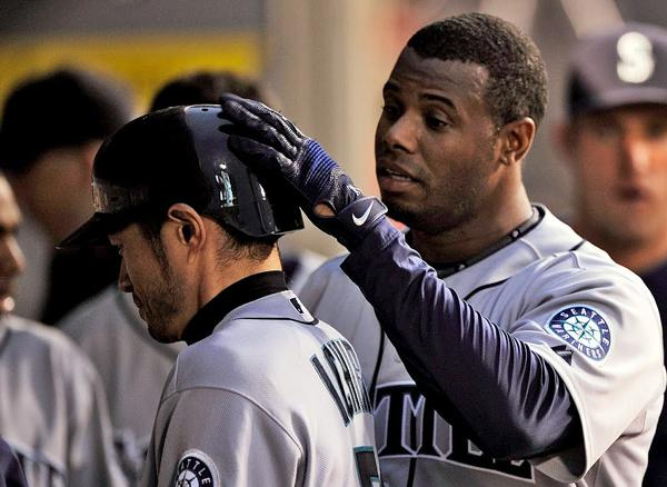Ken Griffey Jr., right, pats Ichiro on the head after he scored on a sacrifice fly by Griffey on May 29, 2009.