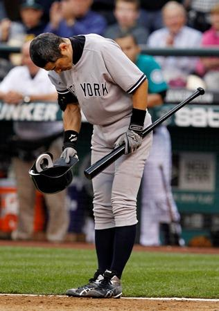 Former Mariner Ichiro Suzuki doffs his batting helmet and bows to fans as he steps up to bat for the first time as a Yankee against the M's in Seattle Monday. It was just hours after the announcement that Ichiro had been traded to New York.