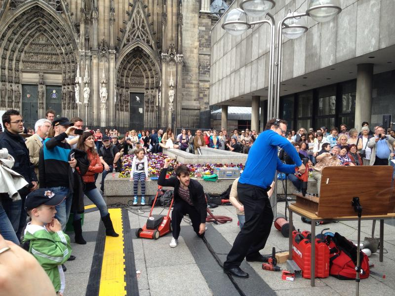 "Baritone Thomas Bonni (in blue) plays a nail gun during the performance of ""EurOratorio - An Experiment based on John Cage's Europeras"" on Roncalliplatz near the Cologne Cathedral."