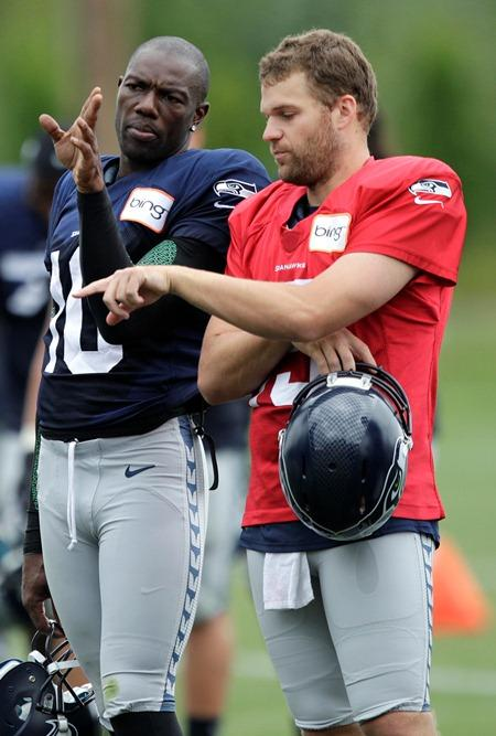 New Seattle Seahawks wide receiver Terrell Owens talks with quarterback Matt Flynn during training camp Wednesday in Renton.