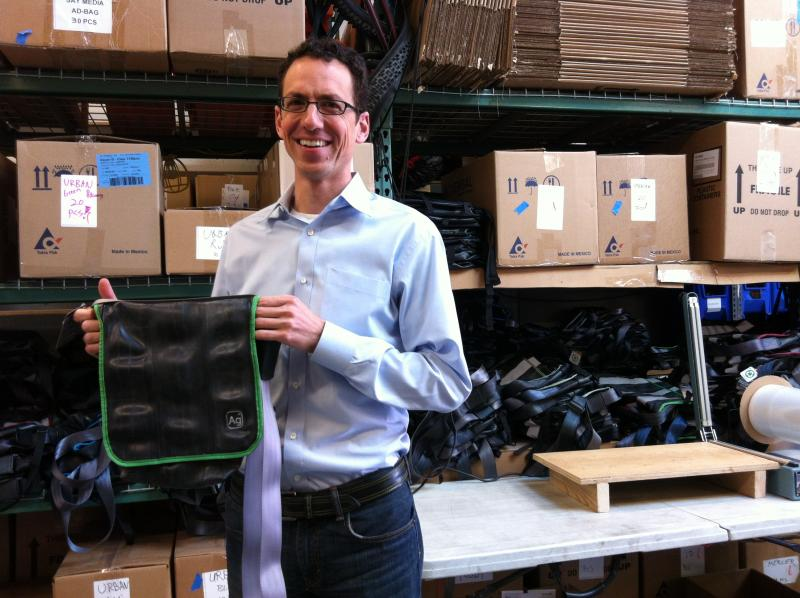 Eli Reich, the owner of Alchemy Goods in Seattle holding one of his company's messenger bags made out of old bicycle tubes.