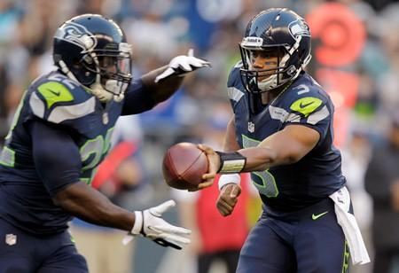 Young guns: Rookie quarterback Russell Wilson hands off to rookie Robert Turbin in a preseason game against the Oakland Raiders.