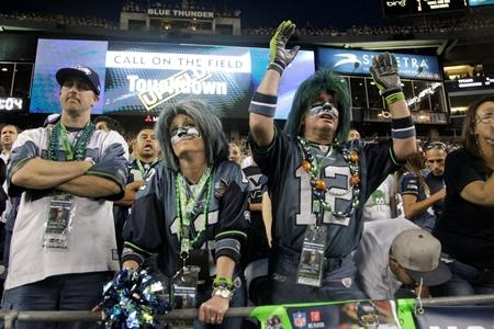 Seahawks fans react to an upheld touchdown by the Tennessee Titans that is shown on the replay screen behind them in a preseason game last month in Seattle.