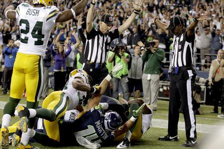 The call seen 'round the world: Officials signal a touchdown by Seahawks wide receiver Golden Tate on the last play of the Monday Night Football match-up against the Green Bay Packers. The call gave the Seahawks a 14-12 win.