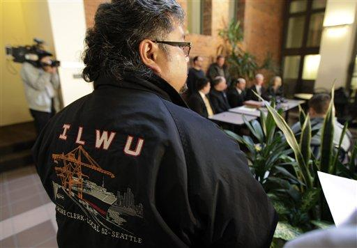 Celso Tolman, vice president of ILWU Local 52, wears a jacket with his union's logo as he listens to attorneys and other union representatives talk to reporters Monday about their intent to file a lawsuit on behalf of the union